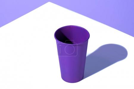 purple plastic disposable cup, on white surface