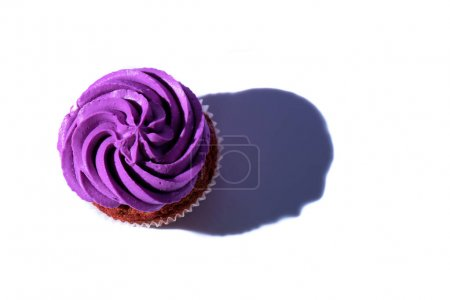 top view of cupcake with purple buttercream icing, on white surface