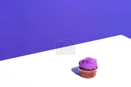 cupcake with purple buttercream glaze, on white surface