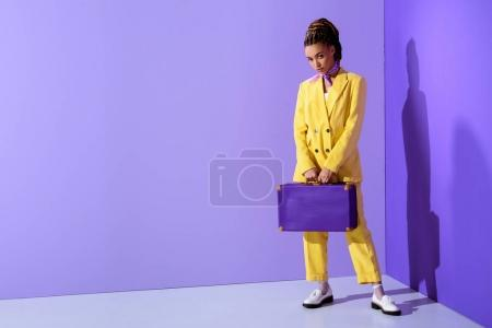 african american girl posing in trendy yellow suit with purple suitcase
