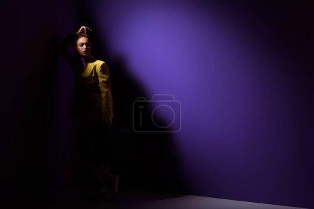 fashionable elegant african american girl posing in dark, on trendy ultra violet background