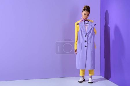 african american girl in yellow suit holding purple waistcoat, on trendy ultra violet background