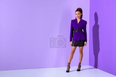 fashionable beautiful mulatto model posing in purple jacket on ultra violet