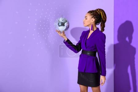 fashionable mulatto girl posing in purple jacket and holding disco ball at ultra violet wall