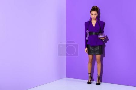 african american girl posing in trendy purple jacket and holding retro rotary phone at ultra violet wall