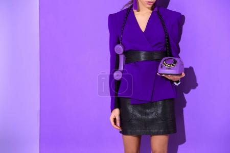 cropped view of elegant girl posing in purple jacket and holding vintage rotary phone at ultra violet wall