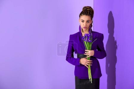 fashionable african american girl posing in purple jacket with irises at ultra violet wall