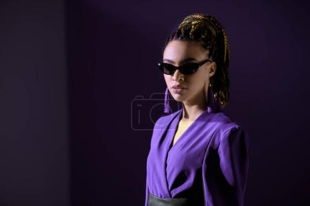 stylish african american girl posing in ultra violet jacket and sunglasses