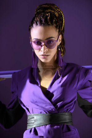 Stylish mulatto girl posing in ultra violet jacket and sunglasses, isolated on purple