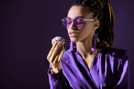 Stylish african american girl in ultra violet jacket and sunglasses with cupcake, isolated on dark purple