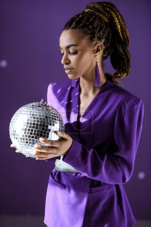 Beautiful african american girl in purple jacket looking at disco ball, isolated on purple