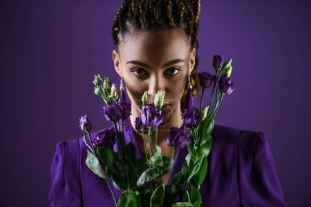 Photo for Stylish mulatto girl posing with purple eustoma flowers, isolated on purple, ultra violet trend - Royalty Free Image