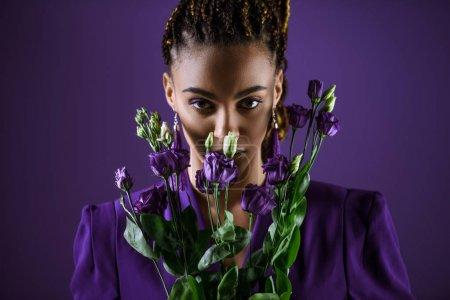 Photo pour Mulâtresse élégant posant avec eustoma violet fleurs, isolées sur violet, ultra tendance violet - image libre de droit