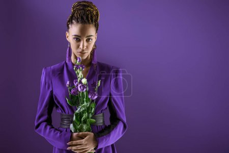 Stylish mulatto model posing with purple flowers, isolated on ultra violet