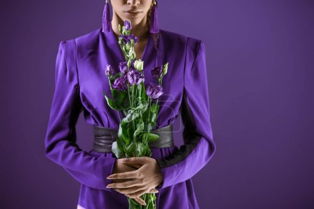 Cropped view of fashionable girl posing in suit with bouquet of flowers, isolated on ultra violet