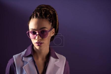 Fashionable african american girl posing in purple sunglasses, isolated on purple