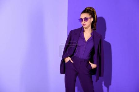 stylish african american girl posing in purple suit and sunglasses, ultra violet trend