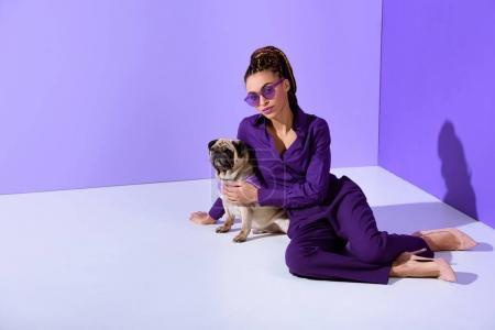 Photo pour Élégant mulâtre fille posant en costume violet à la mode avec chiot carlin, tendance ultra violet - image libre de droit