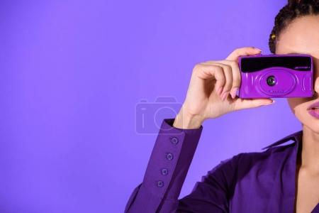Photo for Cropped view of girl in purple jacket taking photo on camera, isolated on ultra violet - Royalty Free Image