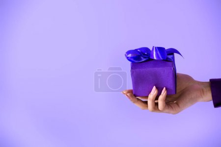 Photo for Cropped view on female hand holding purple gift, isolated on ultra violet - Royalty Free Image