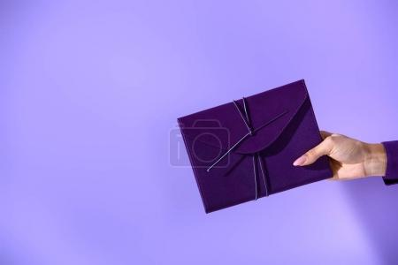 cropped view on woman holding purple diary, on ultra violet