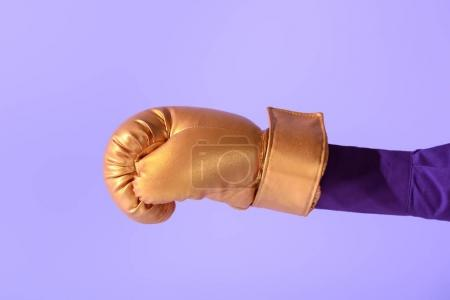 cropped view on female hand in golden boxing glove, isolated on ultra violet