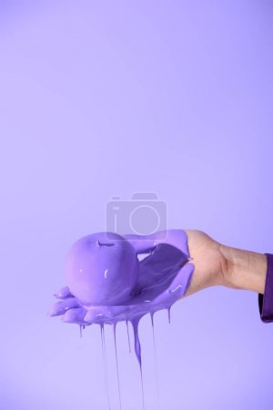cropped view on female hand holding apple in purple paint, isolated on ultra violet