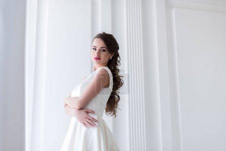 beautiful brunette bride in wedding dress looking at camera