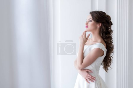 thoughtful young bride in wedding dress