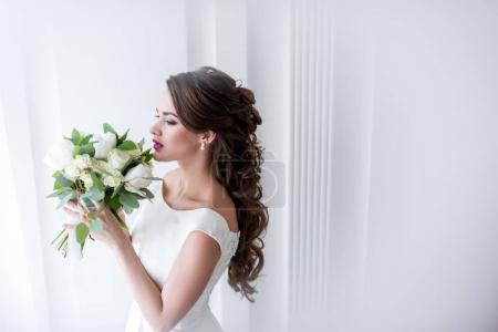 Photo for Attractive bride in white dress sniffing wedding bouquet - Royalty Free Image
