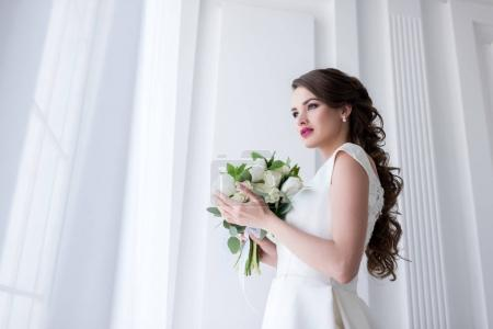 beautiful young bride with wedding bouquet looking at window