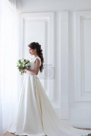 Photo pour Posant dans une robe blanche élégante avec bouquet de mariée de la mariée - image libre de droit