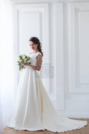 smiling bride posing in elegant dress with wedding bouquet