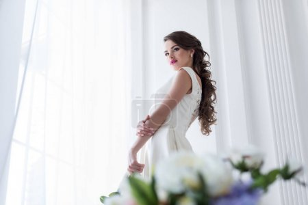 Brunette caucasian bride in wedding dress at window, flowers on foreground