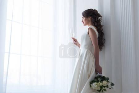 brunette bride in dress with wedding bouquet and glass of champagne looking at window
