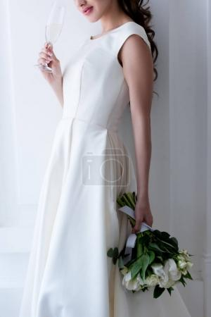 cropped view of bride in elegant dress with wedding bouquet and glass of champagne