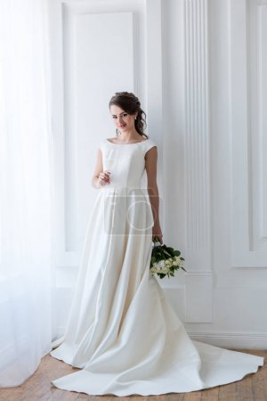 beautiful bride in traditional dress with wedding bouquet and glass of champagne