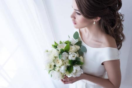 attractive bride in traditional dress holding wedding bouquet