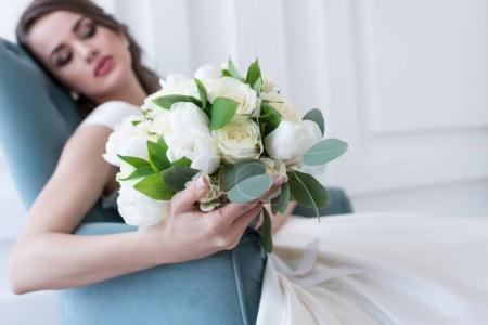 selective focus of bride with wedding bouquet sitting in armchair