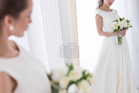 bride in traditional dress with wedding bouquet looking at her reflection in mirror