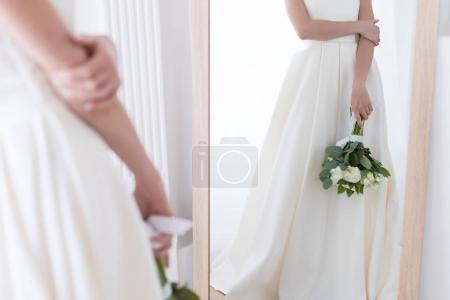 cropped view of bride in traditional dress with wedding bouquet looking at her reflection in mirror