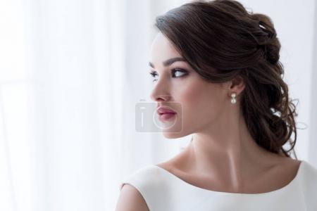 Photo for Attractive brunette woman in white dress looking at window - Royalty Free Image