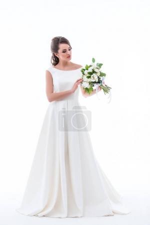 Photo pour Belle mariée posant en robe blanche traditionnelle avec bouquet de mariage, isolé sur blanc - image libre de droit
