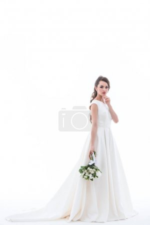 attractive bride posing in traditional white dress with wedding bouquet, isolated on white