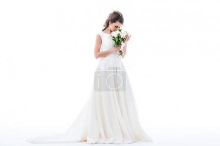 elegant bride posing in traditional dress and sniffing wedding bouquet, isolated on white