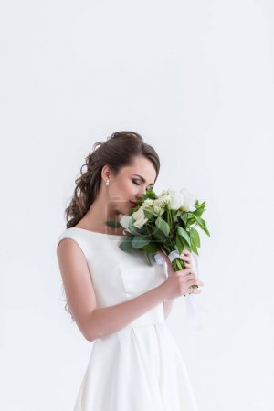 Photo for Attractive bride with closed eyes sniffing wedding bouquet, isolated on white - Royalty Free Image