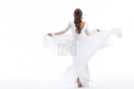 back view of elegant bride dancing in traditional wedding dress, isolated on white