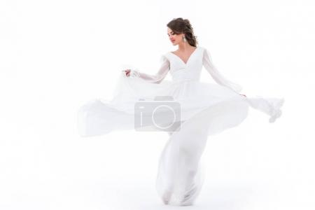 elegant bride dancing in traditional white dress, isolated on white