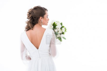 back view of bride in white dress holding wedding bouquet, isolated on white