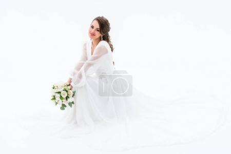 smiling bride in elegant dress holding wedding bouquet, isolated on white